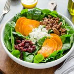 Persimmon and Spinach Salad is baby spinach tossed with sweet persimmon, chewy dried cranberries, creamy goat cheese, and crunchy pecans in an orange maple vinaigrette. It's a delicious fall salad that's perfect for holidays! @FlavortheMoment