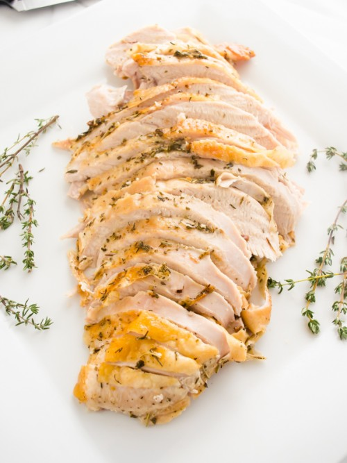 Roast turkey breast with garlic and herbs on a platter