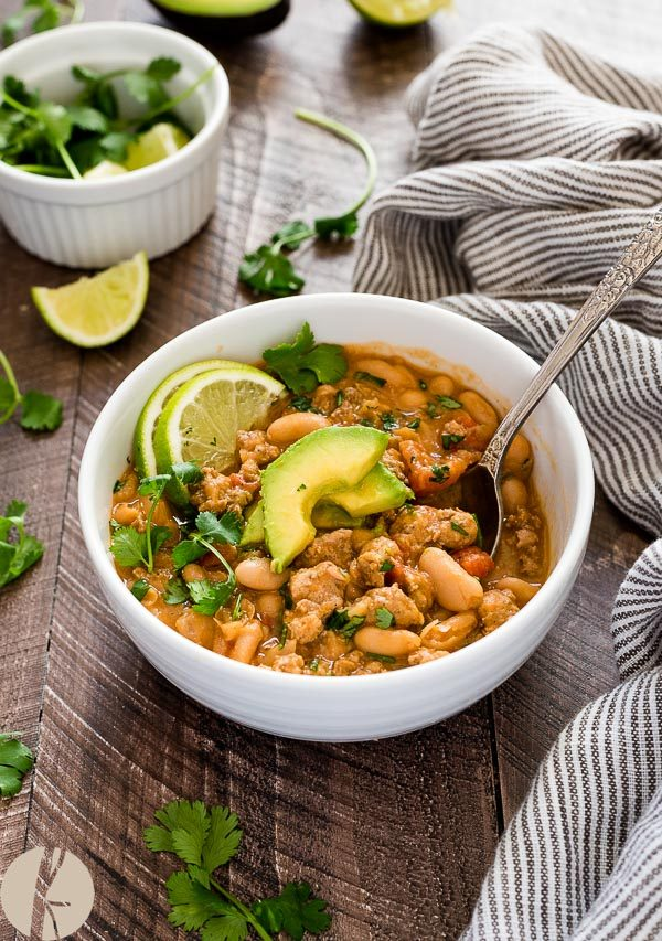 white bean turkey chili in bowl with avocado and lime on top