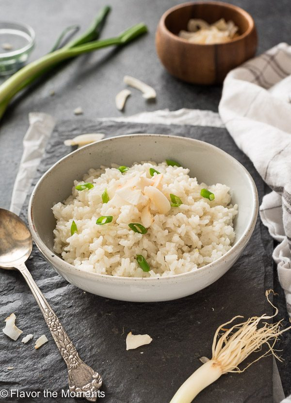 Coconut rice in a bowl with coconut and scallions on top