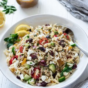 greek orzo salad in a white bowl with spoon buried into the side