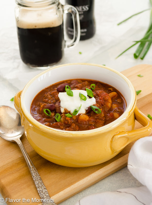Guinness Beef Chili in a bowl with sour cream and scallions on top