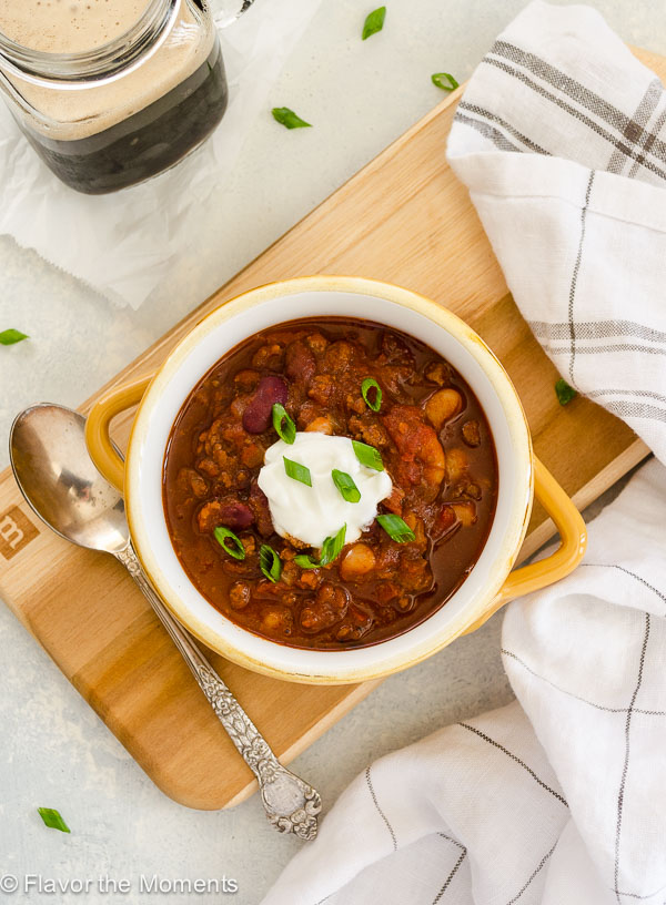 Guinness beef chili in bowl with sour cream and scallions on top