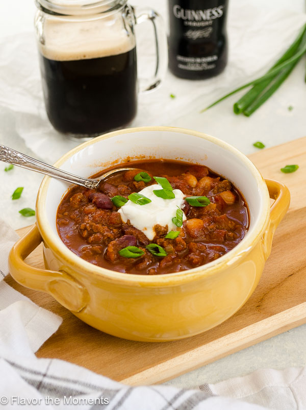 Guinness beef chili in bowl with sour cream and scallions on top and spoon inside