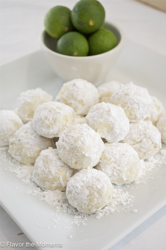Key lime cooler cookies piled on a white plate with limes