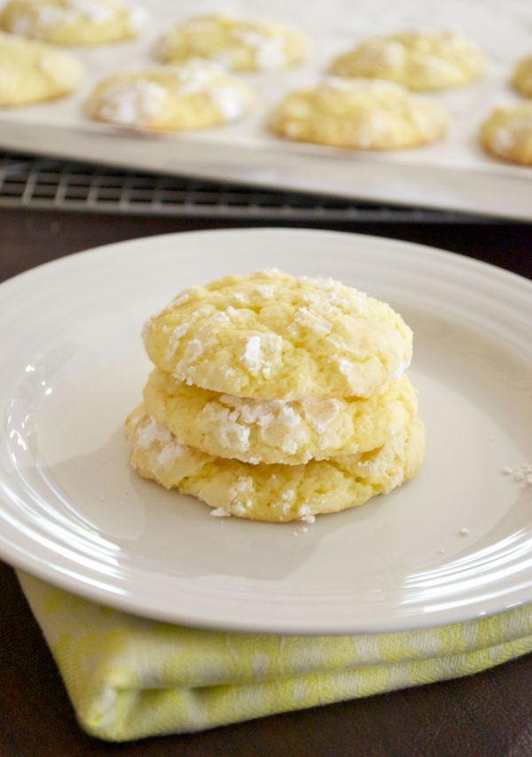 Lemon crinkle cookies stacked on a white plate