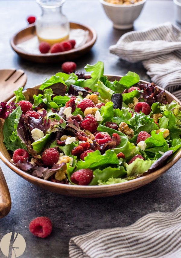 raspberry salad with baby lettuce in teak bowl with servers