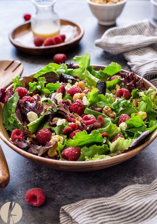 Raspberry feta salad in teak bowl with wooden servers