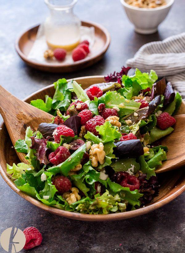 Wooden servers scooping up raspberry feta salad