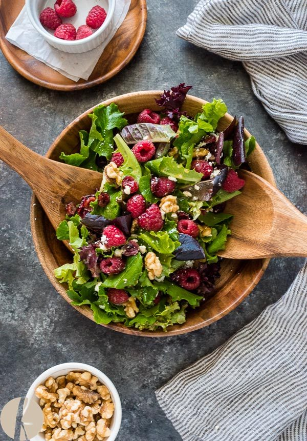 Raspberry salad in teak bowl with wooden servers