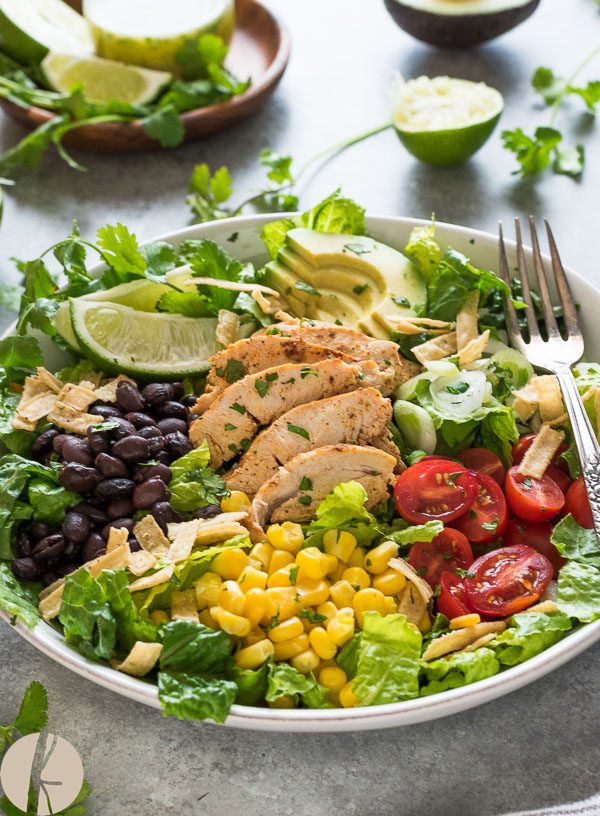 Santa fe chicken salad in white bowl with fork and lime