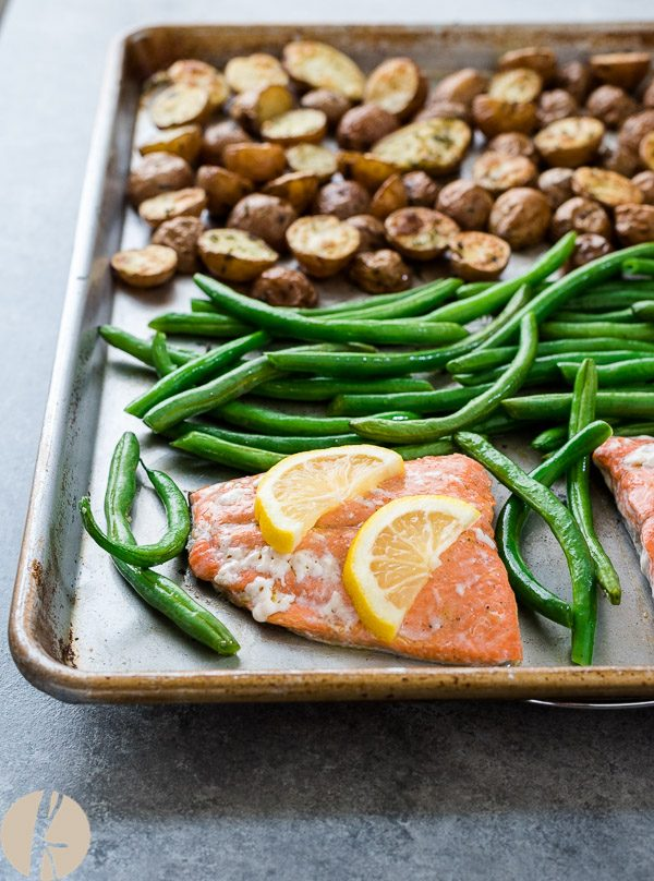 Roasted salmon, green beans and potatoes on baking sheet