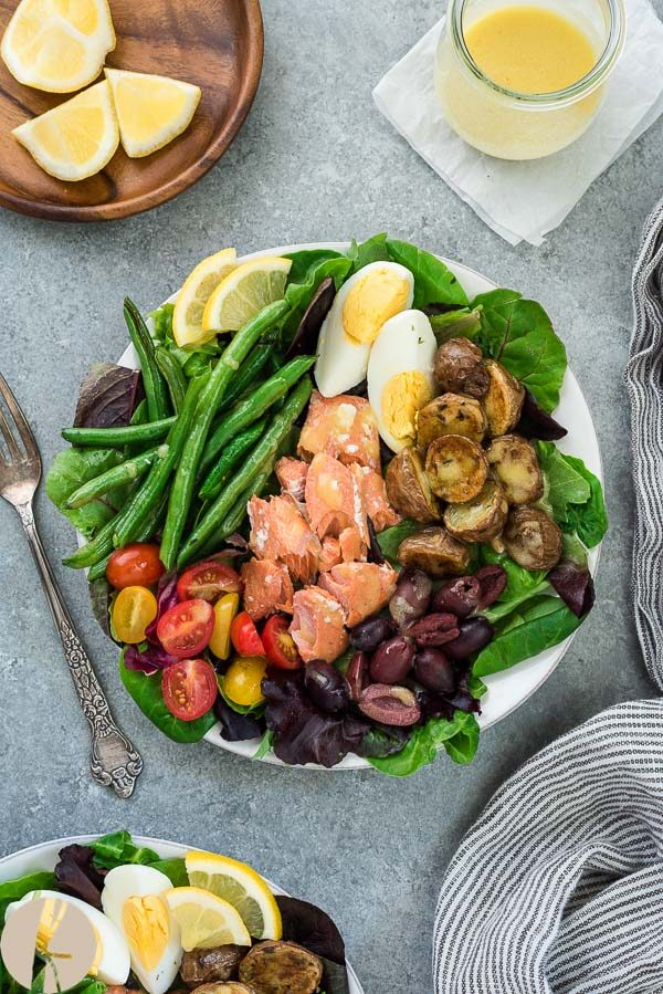 Salmon nicoise salad on white plate with fork and linen alongside