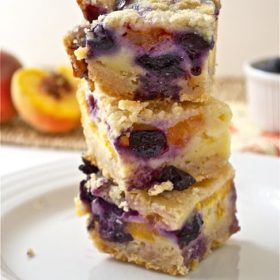 Blueberry peach pie bars stacked up on a plate