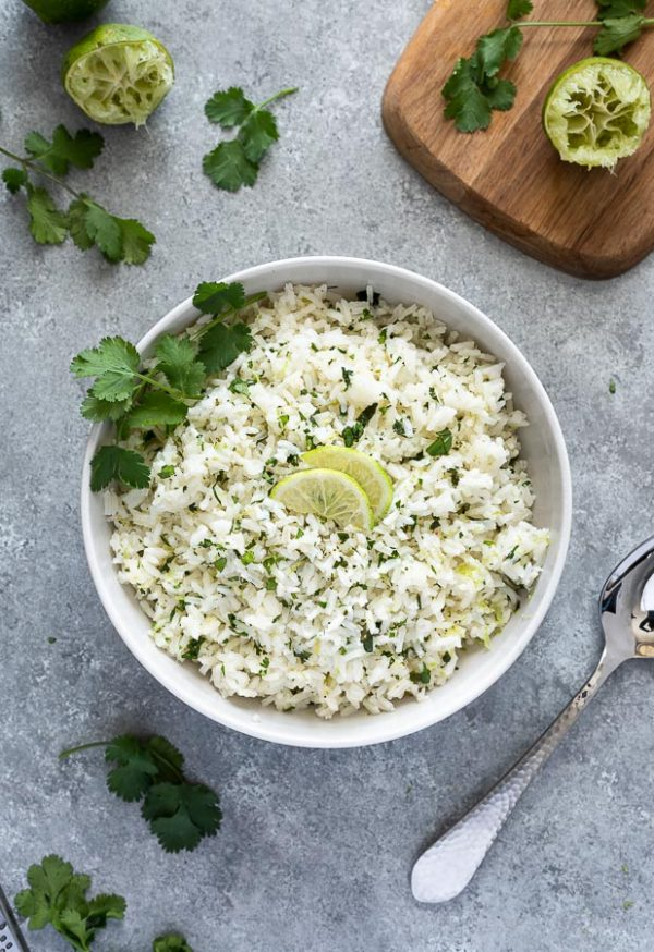 overhead shot of bowl of cilantro lime rice with limes and cilantro on top