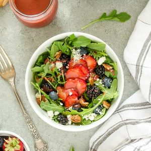 Summer arugula salad with berries in a white bowl
