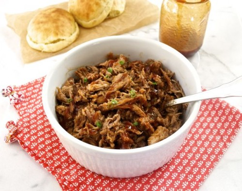 Slow cooker pulled pork in white bowl with spoon