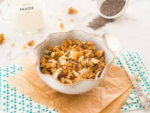 Honey almond granola in bowl on parchment paper