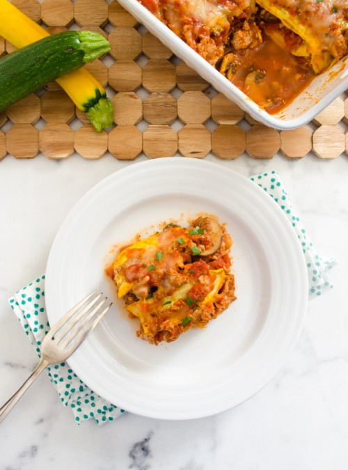 Zucchini lasagna on a white plate with fork