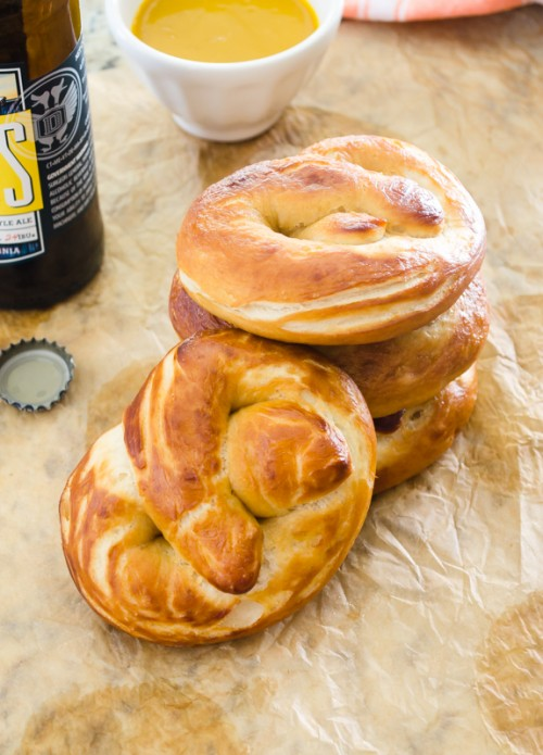 Soft pretzels stacked up and beer bottle in background
