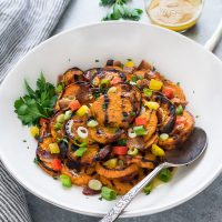 Grilled sweet potato salad in white bowl with spoon