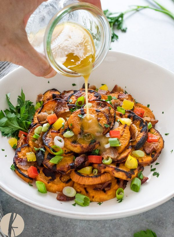 Dressing pouring over grilled sweet potato salad