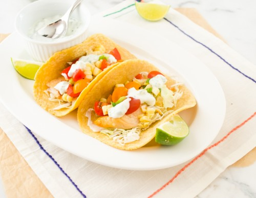 Grilled fish tacos on white plate with salsa and lime