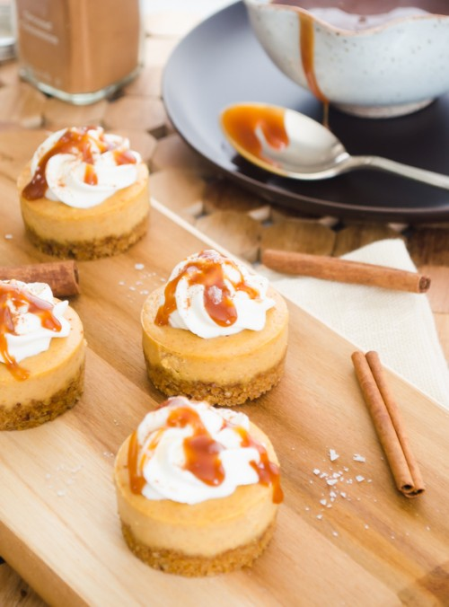 Mini pumpkin cheesecake on wooden board with spoon of caramel sauce