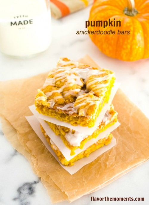 Pumpkin snickerdoodle bars stacked up with pumpkin in background