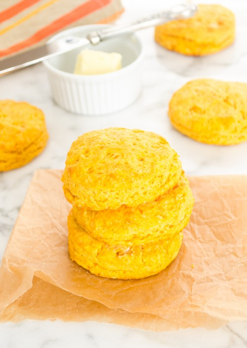 Three sweet potato biscuits piled on top of each other on parchment paper