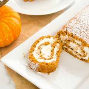 Pumpkin roll cake on white plate with pumpkin alongside