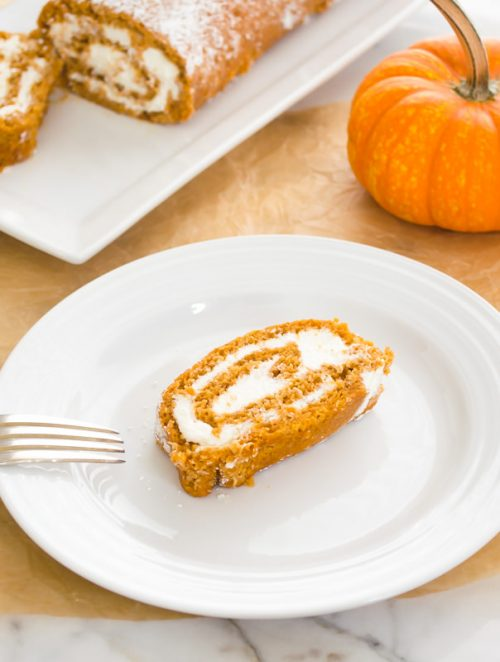 Slice of pumpkin roll cake on white plate with fork