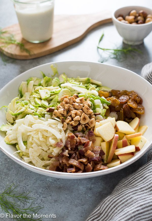 Shaved brussels sprout salad in a bowl before tossing ingredients