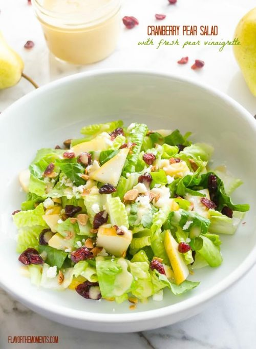 Pear salad in white bowl with cranberries and feta