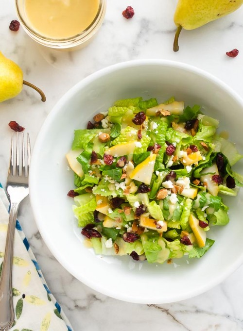 Overhead shot of pear salad in white bowl with fork
