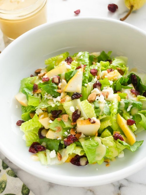 Close up of pear salad in white bowl with cranberries and feta