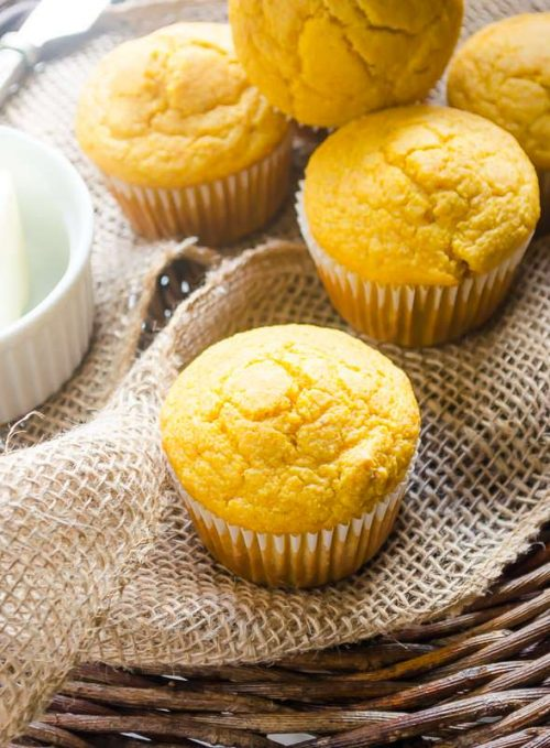Butternut squash cornbread muffins piled on burlap