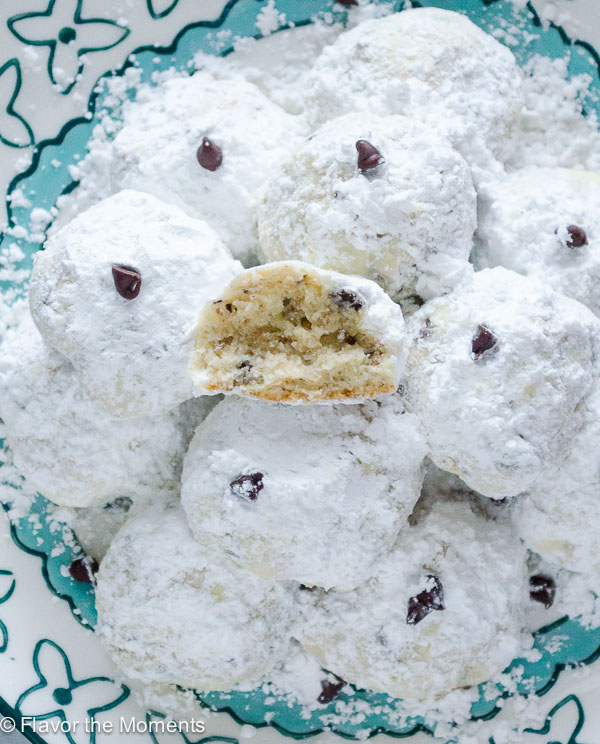 Overhead shot of chocolate chip snowball cookies on a blue plate with top cookie in half