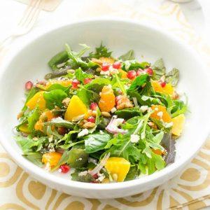 Golden beet orange arugula salad in a white bowl