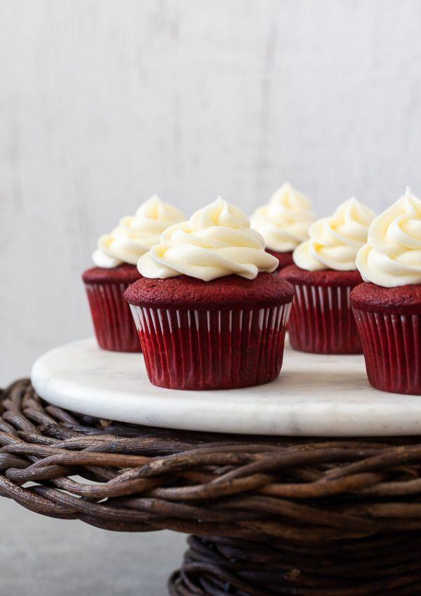 Red velvet cupcakes on wicker pedestal