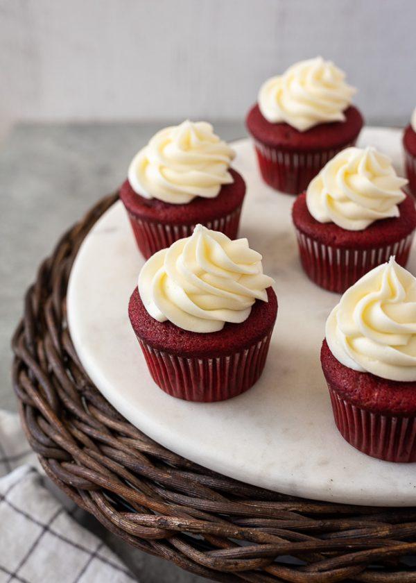 angled overhead shot of red velvet cupcakes on marble server