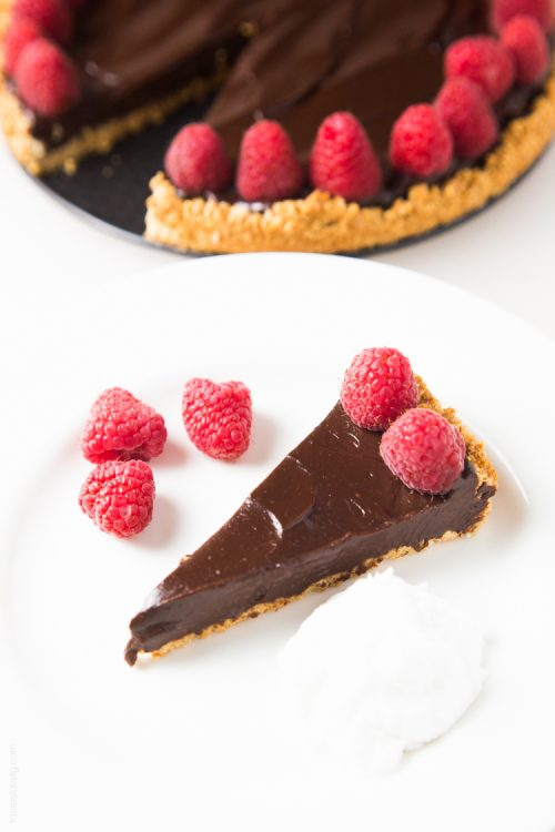 Healthy chocolate tart on a plate with raspberries