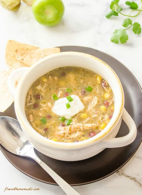 Salsa verde chicken soup in white bowl with sour cream on top