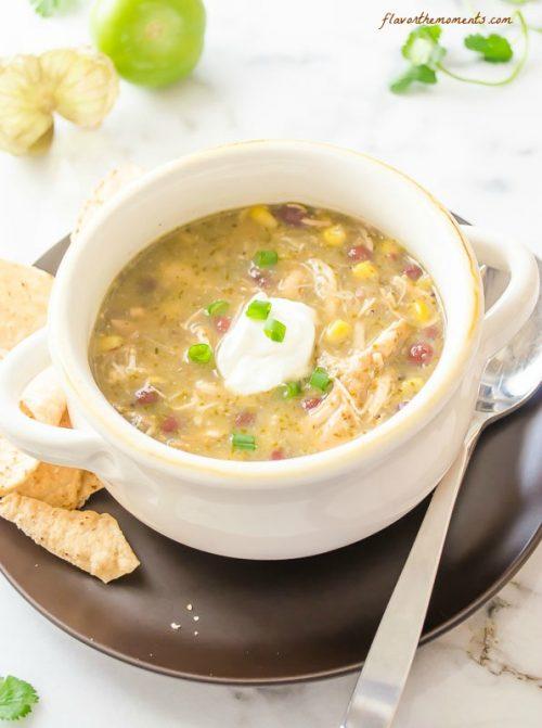 Salsa verde chicken soup in a white bowl