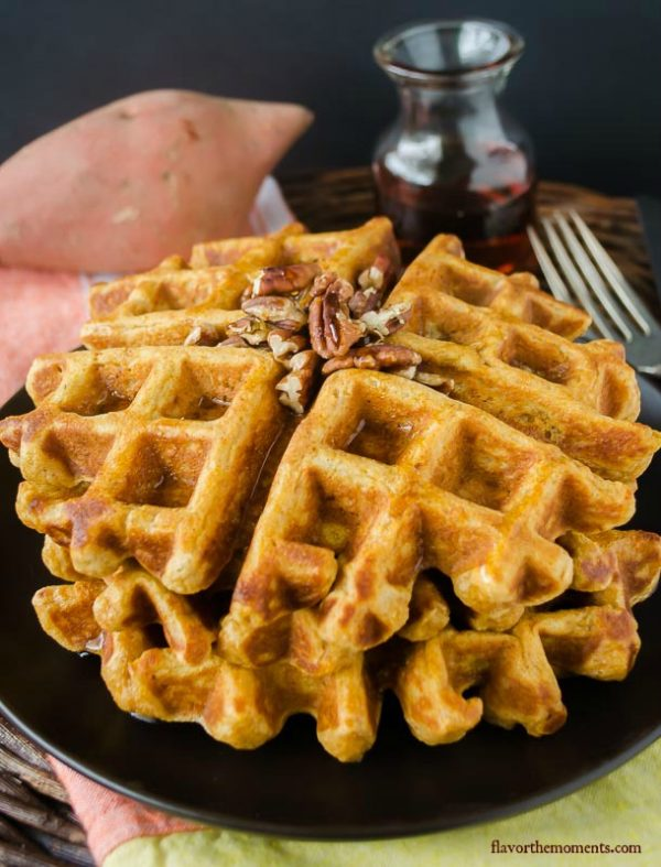 Sweet potato waffles on a plate with pecans on top