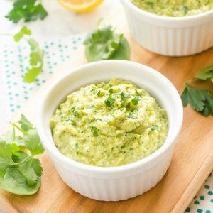 Green hummus in a white ramekin