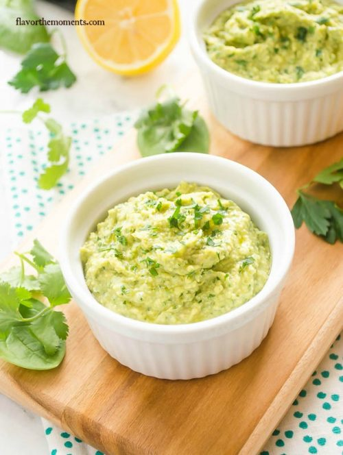 Green hummus in a white ramekin with parsley on top