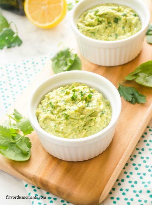 Green hummus in a white ramekin on a cutting board