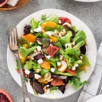 Beet orange salad on white plate with fork
