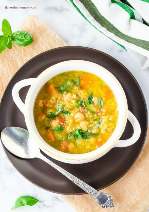 Vegetable quinoa soup in white bowl with spoon